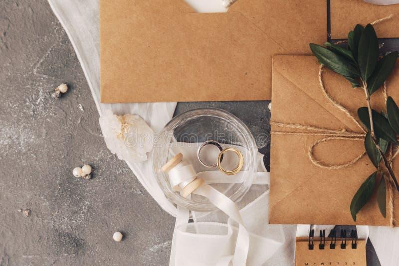 新娘概念礼服婚姻纵向的台阶 在灰色背景的圆环和卡拉服特信封与装饰 库存图片