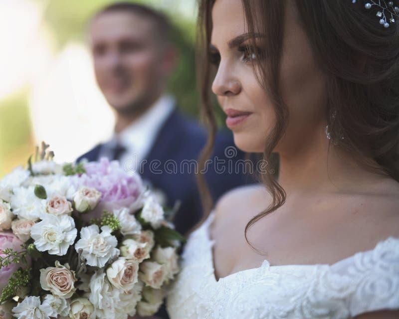 新娘画象拿着婚礼花束和新郎在背景 免版税库存图片