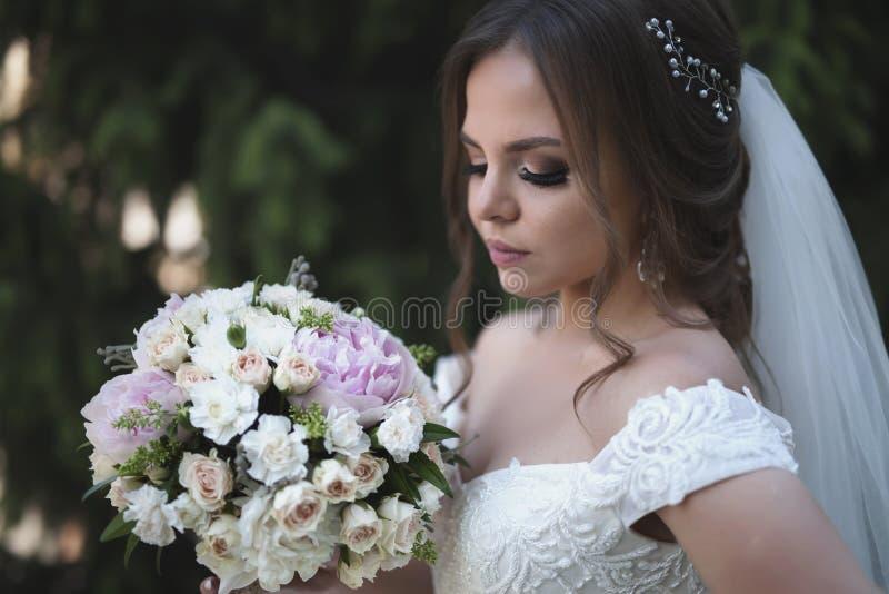 新娘画象拿着婚礼花束在绿色夏天背景 库存图片