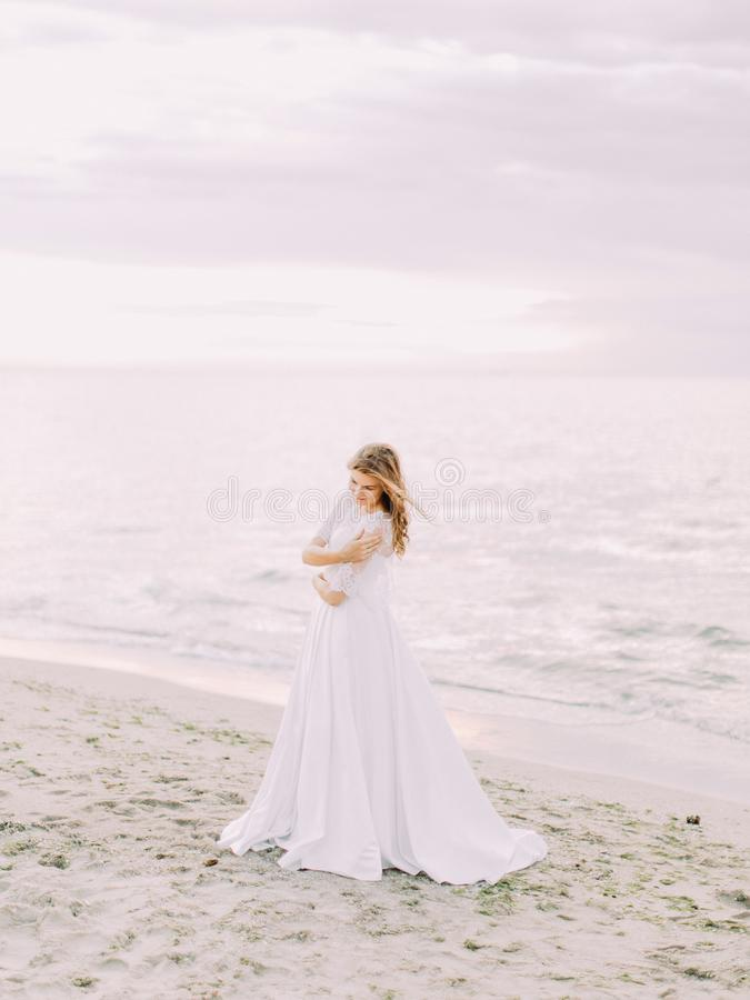 新娘的全长旁边画象长的婚礼礼服的在海的背景在日落期间的 免版税图库摄影