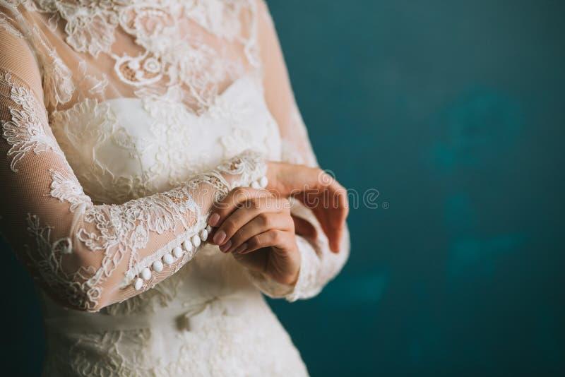 新娘的女性手紧固在袖子的按钮在一个美丽的鞋带白色婚礼葡萄酒礼服特写镜头,早晨preparati 库存图片