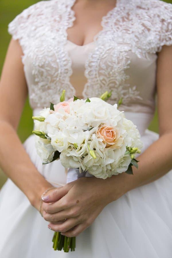 新娘的手有淡粉红的玫瑰和牡丹婚礼花束的  免版税图库摄影