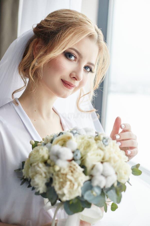 新娘的早晨画象为婚礼做准备 一名白肤金发的妇女的画象在窗口附近的在一件白色长袍 免版税图库摄影
