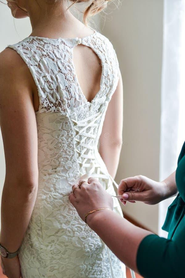新娘的早晨,当她穿一件美丽的礼服,准备好的妇女在婚礼前 免版税库存图片