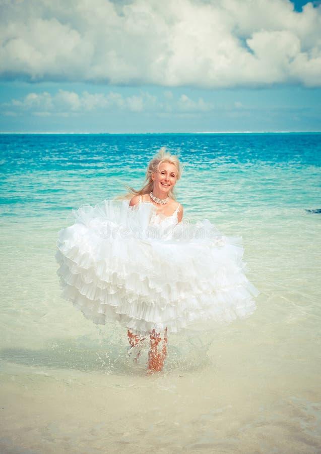 新娘的礼服的年轻美丽的妇女在海的波浪跑,有一个减速火箭的作用的 免版税库存图片