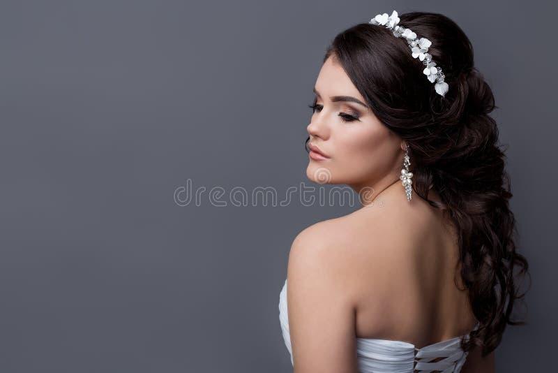 新娘的美丽的柔和的女孩画象一套白色婚礼礼服的与与花外缘的晚上发型在她的头发的和 库存照片