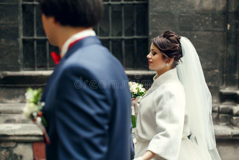 新娘看起来华美走在有新郎的城市附近 库存图片