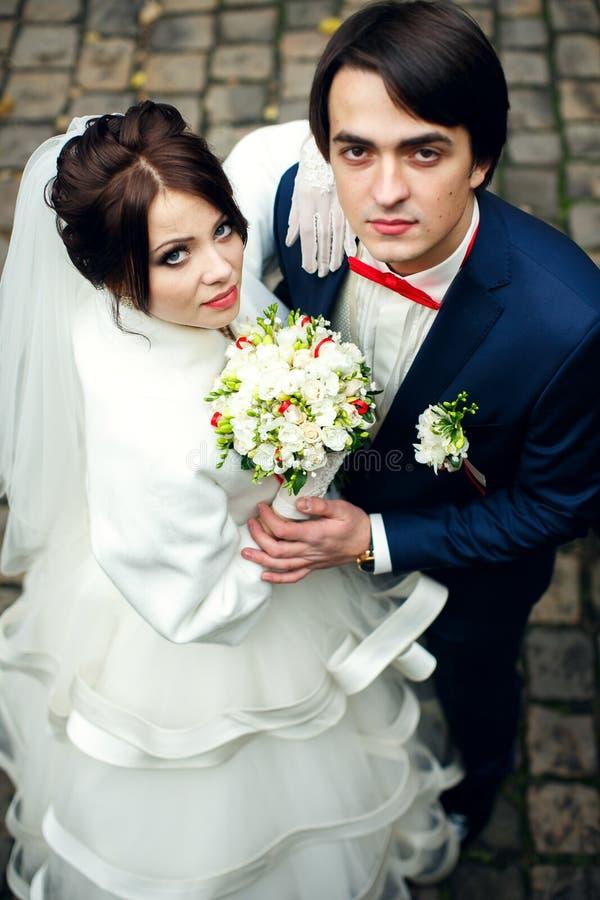 新娘看起来在新郎后的确信的身分 免版税库存图片