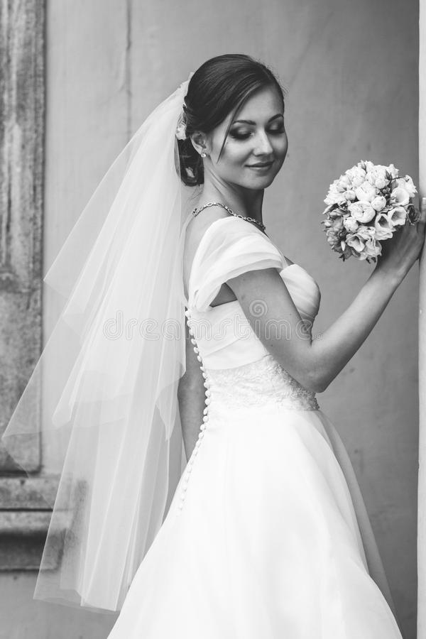 新娘看起来害羞摆在石台阶 免版税库存图片