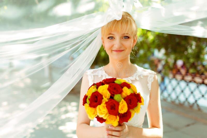 新娘看起来害羞的藏品黄色和英国兰开斯特家族族徽花束  免版税库存图片