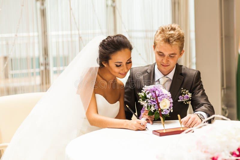 新娘签署的结婚证书或婚姻的合同 免版税库存照片
