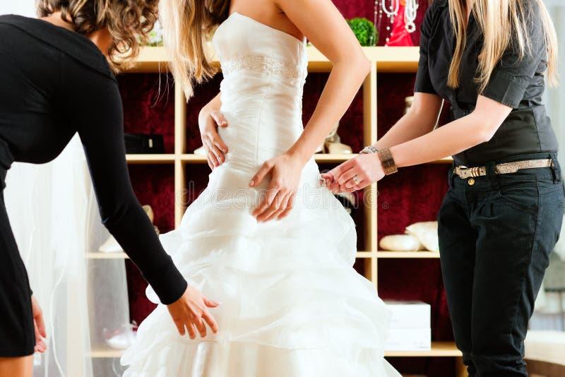 新娘给女装店婚礼穿衣 免版税库存图片