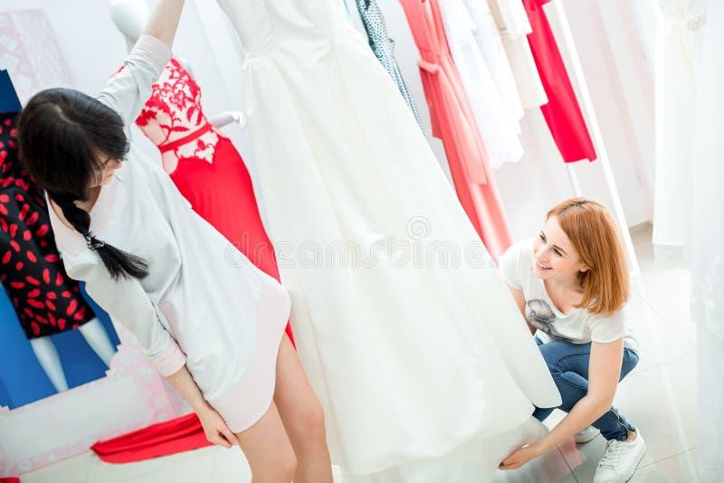 新娘选择婚礼礼服 免版税库存照片