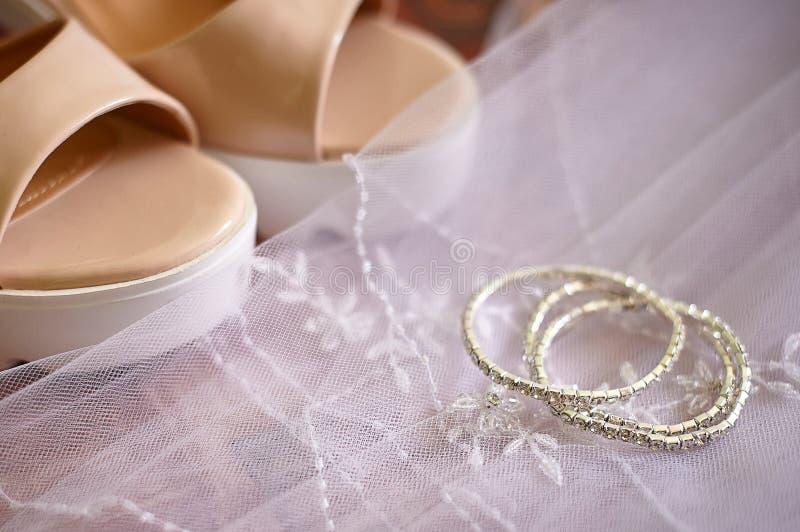 新娘鞋子和婚礼辅助部件在面纱的背景 免版税库存照片