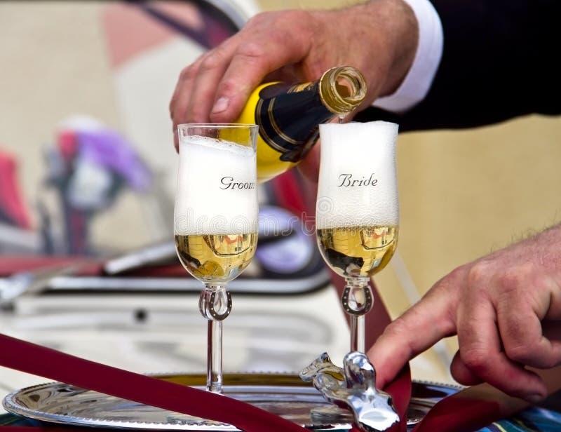新娘香槟倾吐对婚礼的玻璃新郎 免版税图库摄影