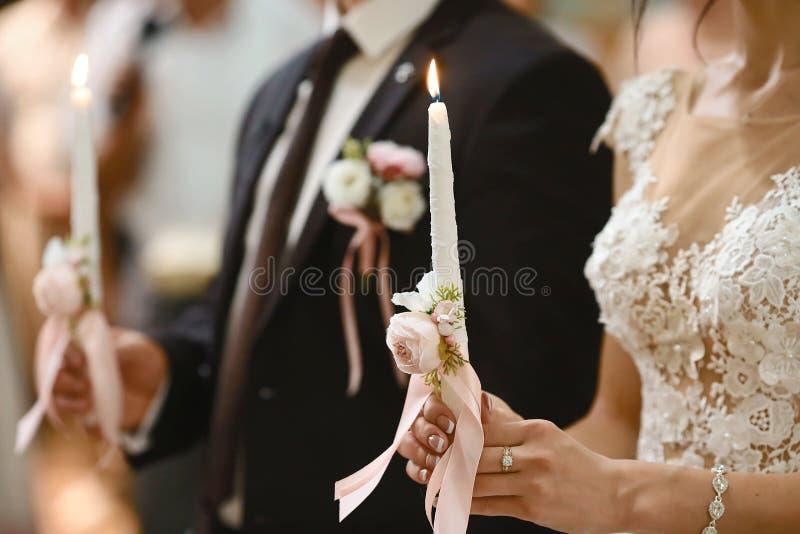 新娘,举行婚姻蜡烛的新郎在手上 烧伤蜡烛 举蜡烛的精神夫妇在基督徒的婚礼期间 库存照片