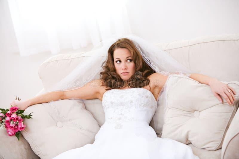 新娘:懊恼新娘坐有花束的长沙发 免版税库存照片
