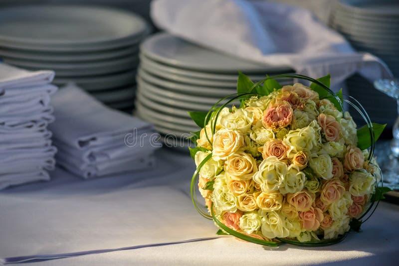 新娘-五颜六色的花桃红色,说谎在桌上的白玫瑰和黄色小苍兰婚礼花束自然夏日 图库摄影