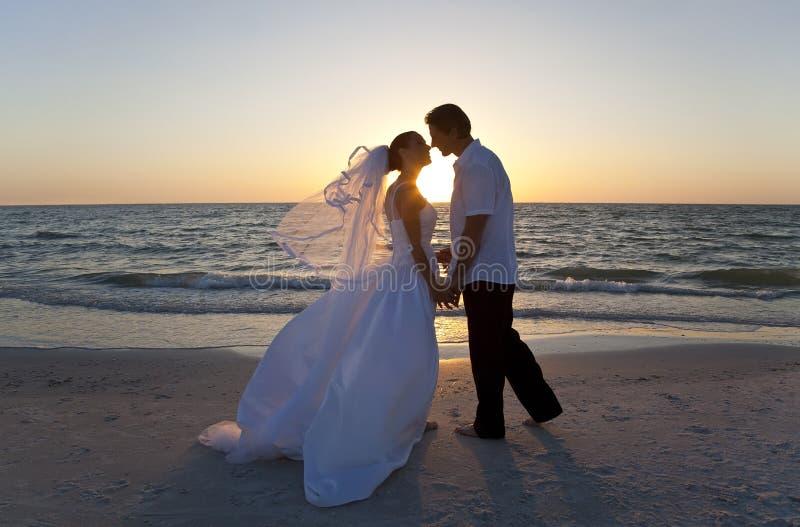 新娘&新郎夫妇亲吻的日落海滩婚礼 免版税库存图片