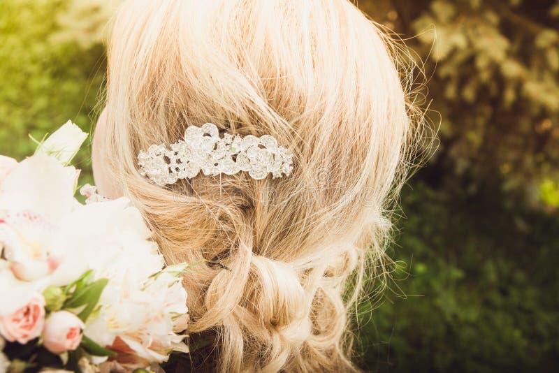 新娘` s发型的特写镜头在她的手上的拿着花束在自然背景 图库摄影