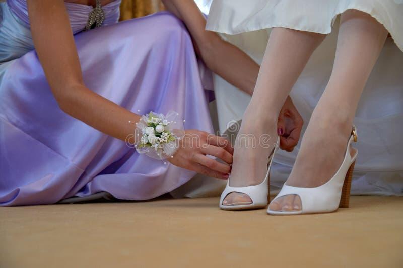 新娘` s白色鞋子和女傧相` s手特写镜头  早晨r 库存图片