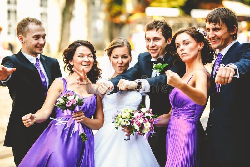 新婚佳偶与他们的朋友一起站立在步行期间  免版税图库摄影