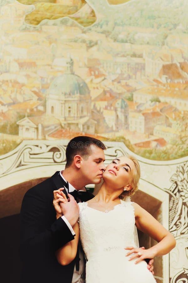 新婚佳偶亲吻在墙壁后的身分有城市壁画的 库存图片