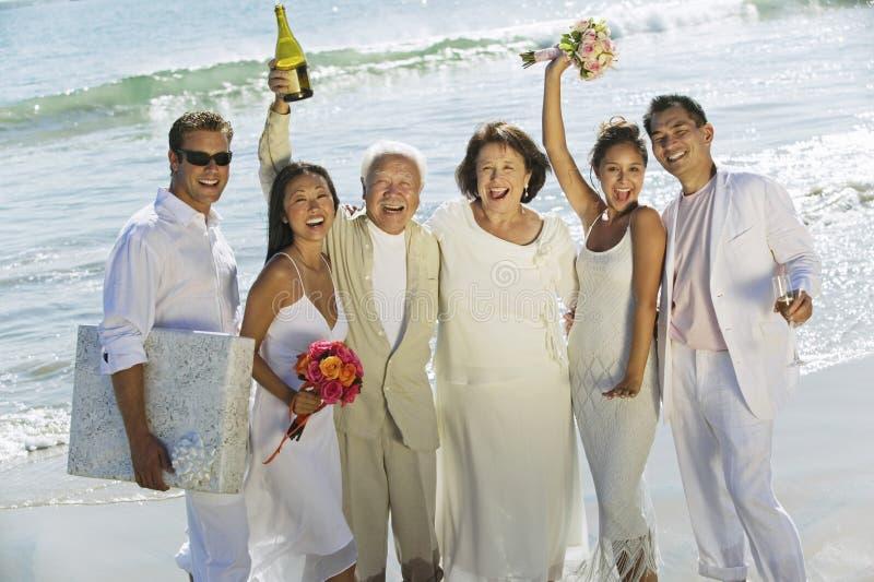 新婚佳偶加上庆祝在海滩的家庭 免版税库存图片