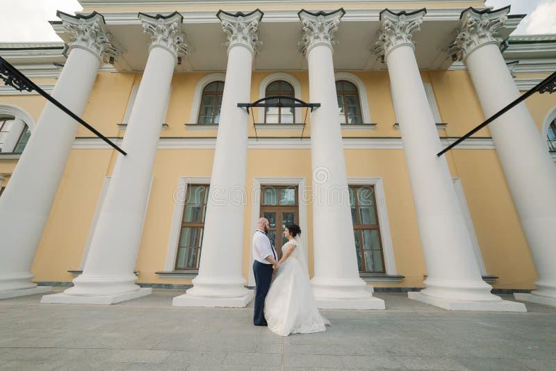 新婚佳偶在他们的婚礼那天在公园走,看彼此,微笑 免版税库存照片