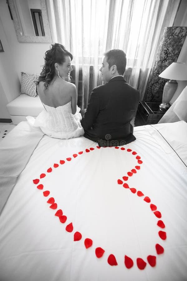 新婚佳偶在有红色瓣心脏的卧室 黑色白色 免版税库存图片