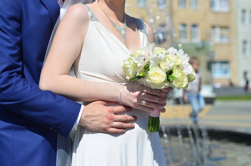 新婚佳偶夫妇拿着美丽的婚礼花束 古典婚礼摄影,象征团结、爱和creati 免版税库存图片