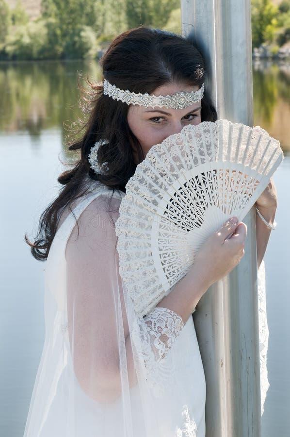 新婚佳偶妇女摆在与她的ââ¬â ¹ ââ¬â ¹风扇 图库摄影