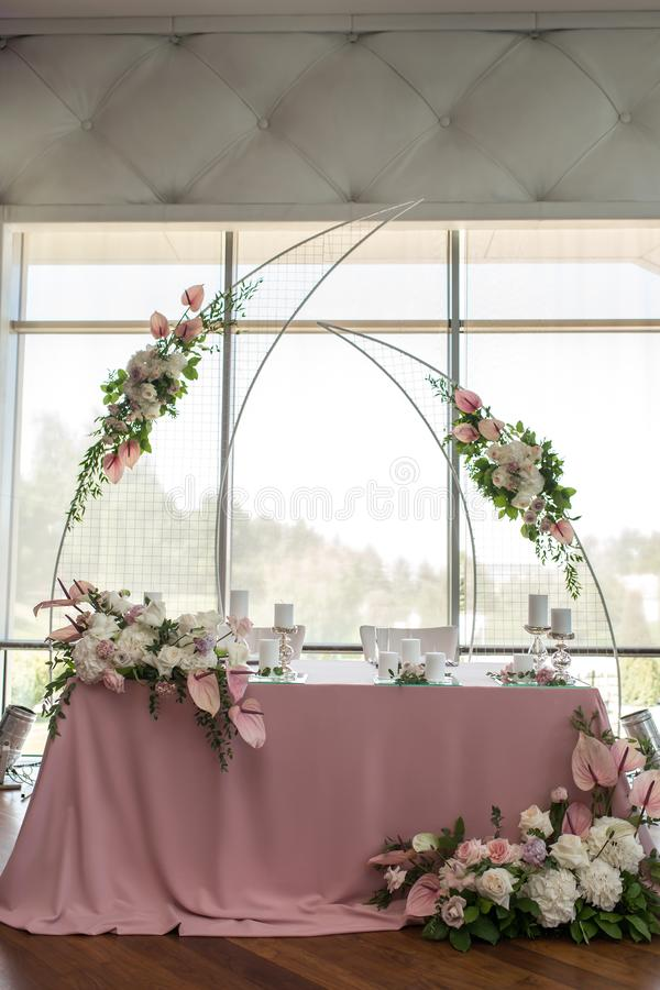 新婚佳偶宴会用鲜花和蜡烛装饰的桃红色桌 婚礼装饰概念 免版税库存图片