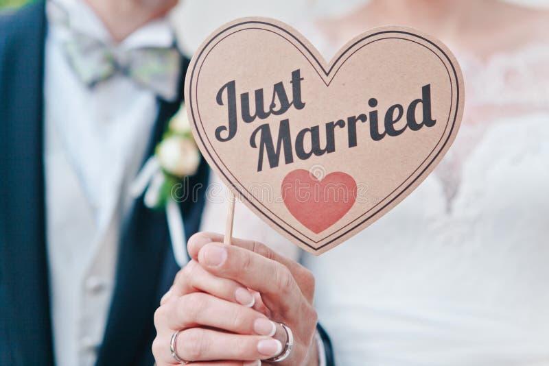 新婚佳偶手特写镜头拿着标志的说结婚的,选择聚焦 免版税库存照片