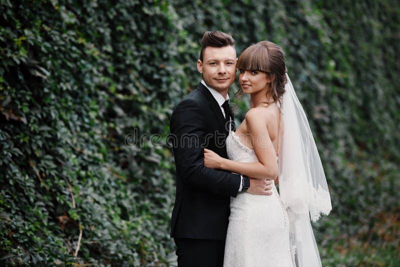 新婚佳偶时髦的夫妇在他们的婚礼那天 愉快的年轻新娘、典雅的新郎和婚姻的花束 免版税库存照片