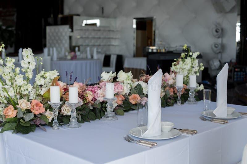 新婚佳偶桌在餐馆装饰鲜花和蜡烛 婚姻的鲜花装饰 库存照片
