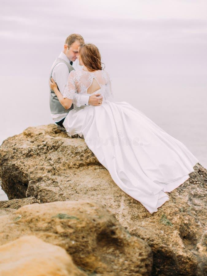 新婚佳偶的垂直后面视图势均力敌坐峭壁在海的背景 免版税库存照片