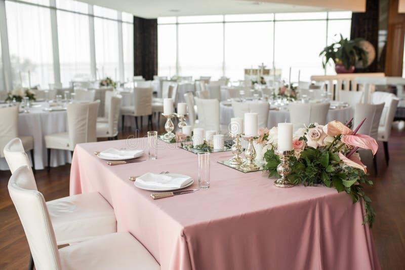 新婚佳偶的婚姻的桌设置用康乃馨、玫瑰、安祖花和玉树叶子鲜花装饰 库存图片