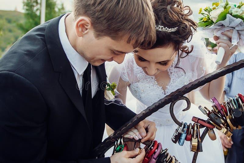新婚佳偶紧固在恋人桥梁的锁  中断玻璃人传统婚礼 免版税库存图片