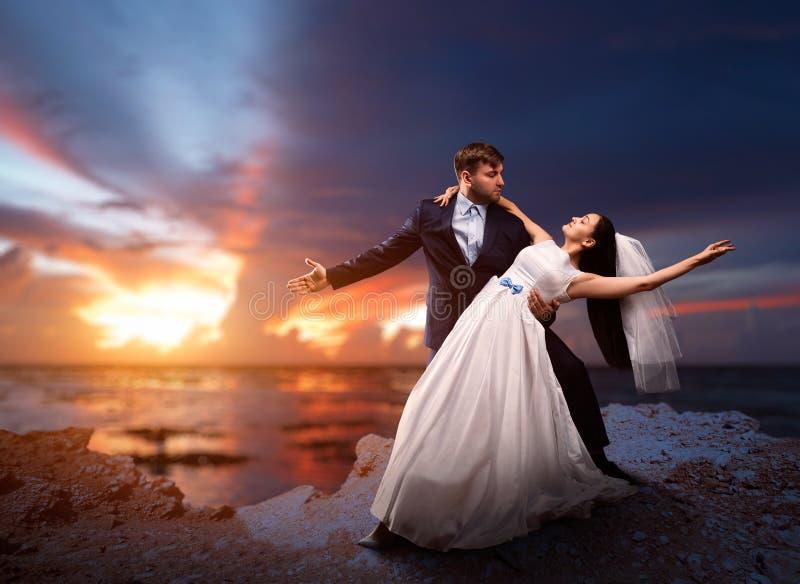新婚佳偶跳舞,海和日落在背景 免版税图库摄影