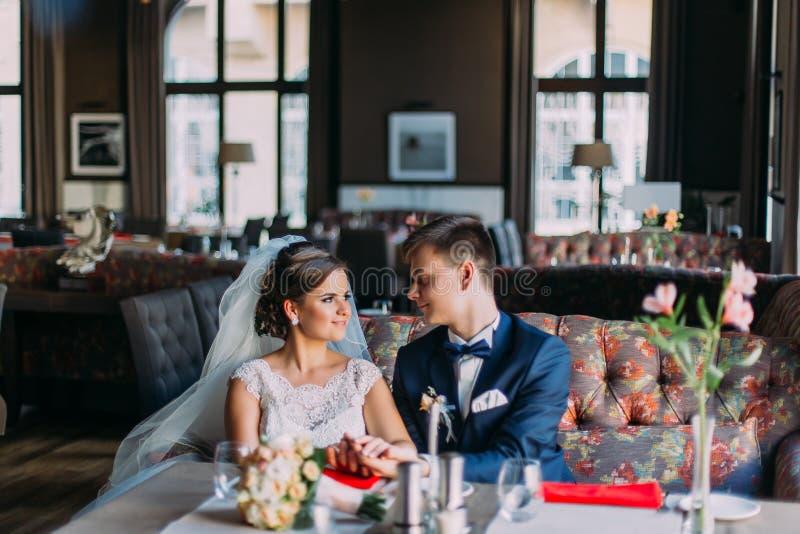 新婚佳偶enloved夫妇 坐在她的丈夫蓝色随员旁边的白色礼服的美丽的年轻妻子摆在户内 免版税图库摄影