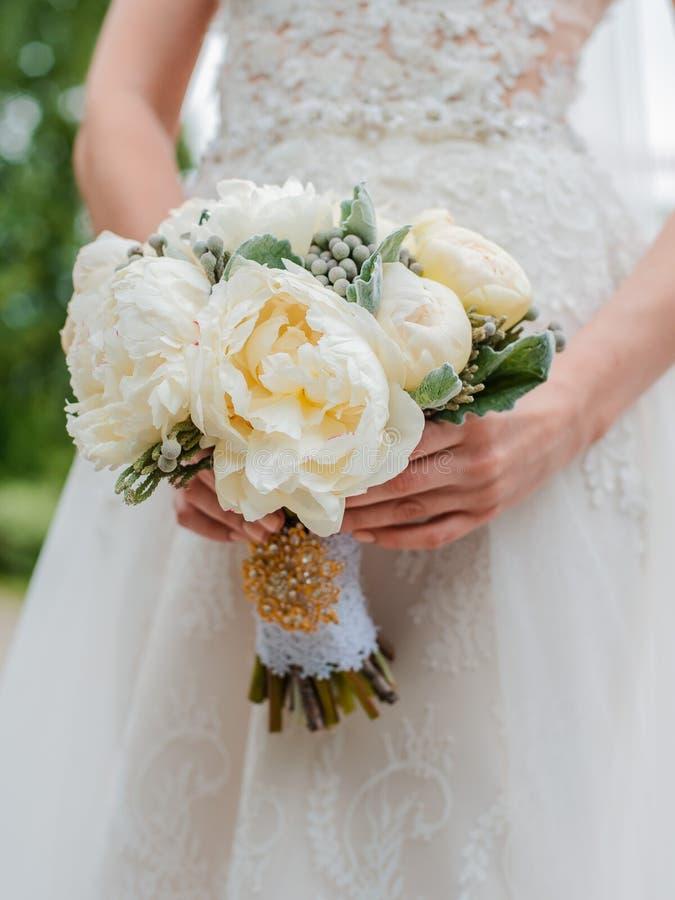 新婚夫妇 结婚日 新娘手上的花束,新郎的拥抱 免版税库存照片