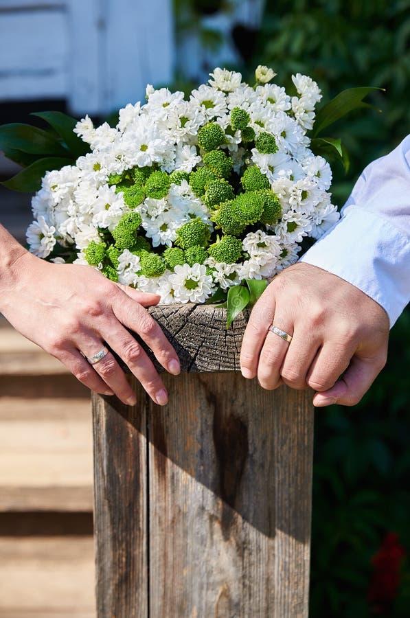 新婚的夫妇的手在说谎在自然老木板条的白色装饰雏菊旁边婚姻的花束的  库存照片
