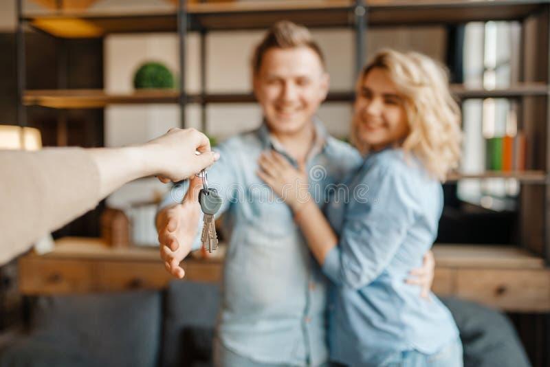 新婚的爱夫妇接受作为礼物钥匙 免版税库存图片