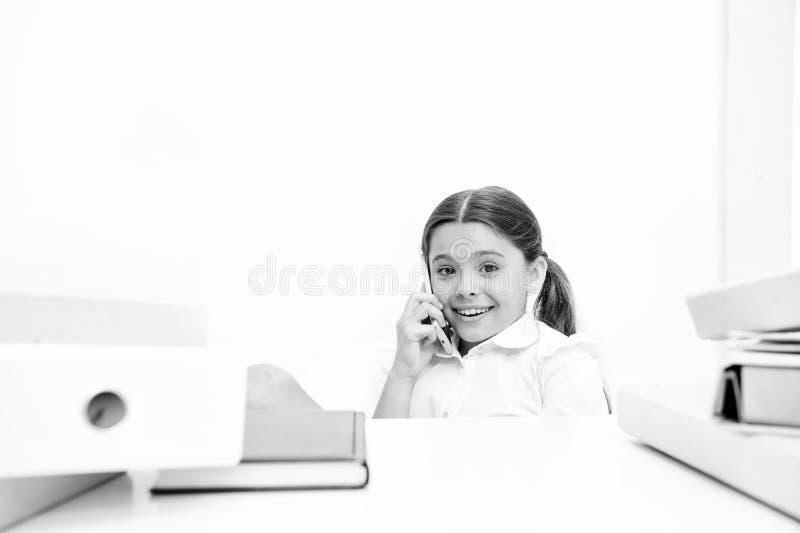 新学校闲话 她喜欢谈太多 谈论谣言 逗人喜爱的闲话女孩 女小学生笑容谈论 库存照片