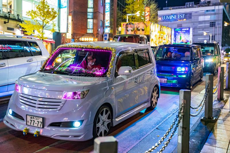 新宿,东京,日本- 2018年12月24日:有五颜六色的LED的逗人喜爱的汽车装饰照明设备在圣诞节庆祝的夜街道 图库摄影