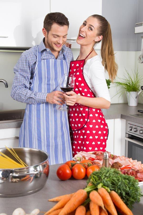 年轻新已婚夫妇在一起烹调的厨房里 免版税图库摄影