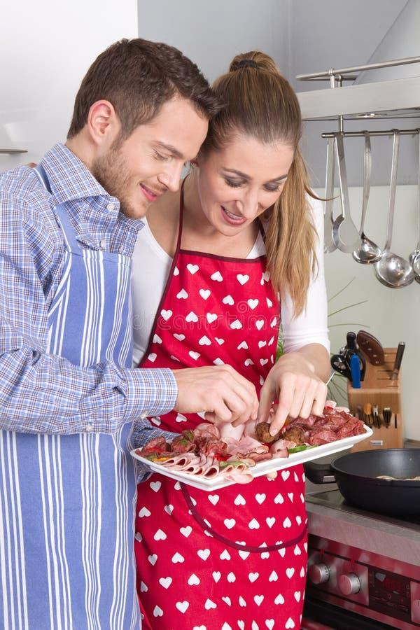 年轻新已婚夫妇在吃香肠的厨房里 免版税库存照片