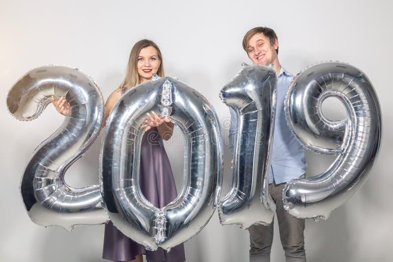 新年、庆祝和假日概念-拿着标志2019的滑稽的爱夫妇由银色气球制成新年  库存图片