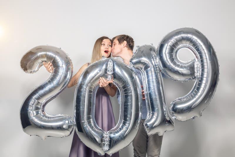 新年、庆祝和假日概念-拿着标志2019的滑稽的爱夫妇由银色气球制成新年  免版税库存照片